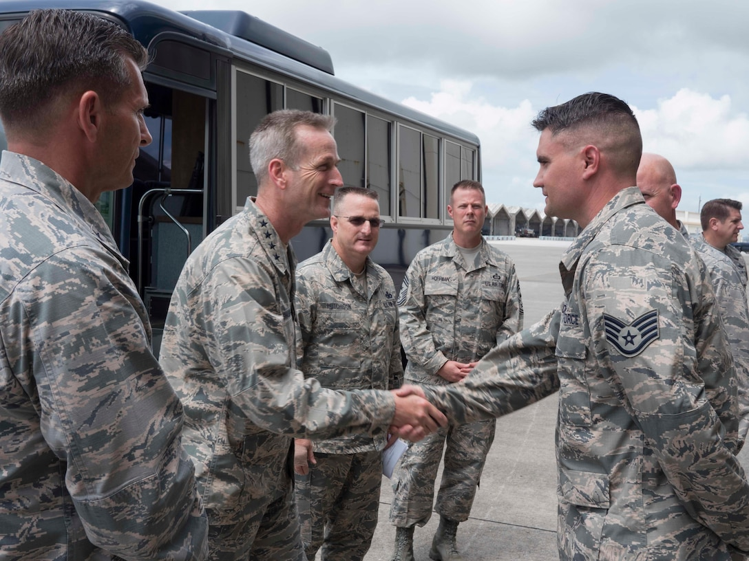 U.S. Air Force Gen. Terrence J. O'Shaughnessy, Pacific Air Forces commander, coins U.S. Staff Sgt. Daniel Tondre, 18th Munitions Squadron assistant noncommissioned officer in charge, for his hard work and dedication to his job at Kadena Air Base, Japan, Aug. 11, 2016. During his visit to the base, the general presented coins to several Airmen from Kadena in honor of their outstanding performance and dedication to the mission. (U.S. Air Force photo by Senior Airman Omari Bernard)