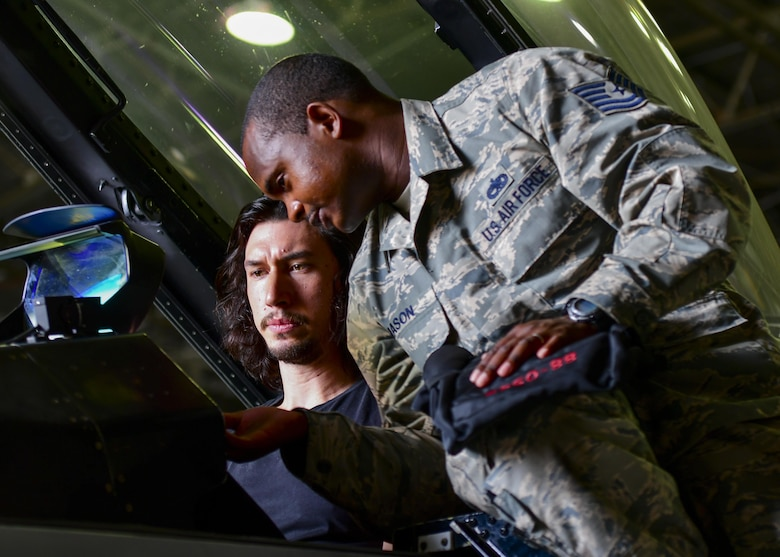 "Tech. Sgt. Antonio Mason, 51st Aircraft Maintenance Squadron crew chief, explains F-16 Fighting Falcon controls to actor Adam Driver at Osan Air Base, Republic of Korea, Aug. 13, 2016. Driver and several other actors visited base and learned about the Team Osan mission before performing a reading of the play ""Lobby Hero"" here. (U.S. Air Force photo by Senior Airman Victor J. Caputo/Released)"