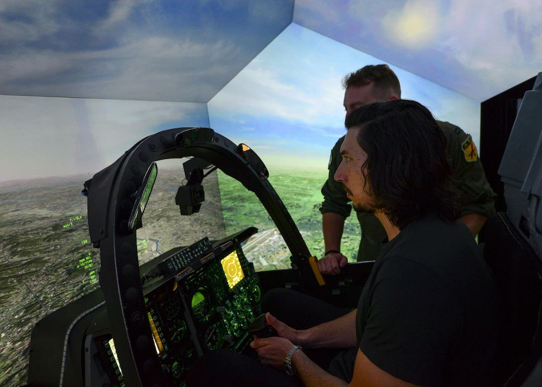 """Actor Adam Driver operates the A-10 Thunderbolt II flight simulator at Osan Air Base, Republic of Korea, Aug. 13, 2016. Driver visited base to perform a reading of the play """"Lobby Hero"""" alongside several other actors, and was given insight to the importance of the Team Osan mission. (U.S. Air Force phot by Senior Airman Victor J. Caputo/Released)"""