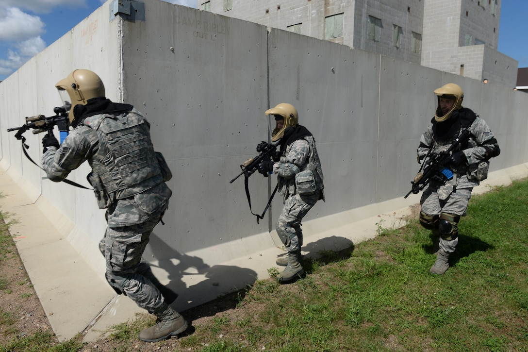 Senior Airman Lukas Brendemuhl, left, leads fellow 119th Security Forces Squadron Airman 1st Class Pamela Fehr and Senior Airman Joshua Nistler around a corner as they pursue a simulated adversary during a force on force training scenario at the Camp Ripley military operations on urban terrain (MOUT) village Aug. 13, 2016. The Camp Ripley MOUT village provides a realistic environment for the security forces personnel to practice tactics they would use in deployed locations. They are firing M-4 weapons loaded with simunition rounds that are similar to paintball rounds, so they can identify adversaries that have been hit. (U.S. Air National Guard Photo by Senior Master Sgt. David H. Lipp)