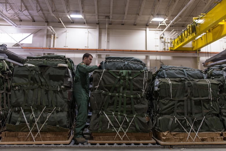 U.S. Air Force Senior Airman Andrew Fox, 36th Airlift Squadron joint airdrop inspector, inspects the parachute on a container delivery system bundle during Red Flag Alaska on Joint Base Elmendorf-Richardson, Alaska, Aug. 11, 2016. JAI's must perform two inspections; one before loading to ensure cargo is aircraft ready and rigged in accordance with proper rigging procedures and an after inspection of the cargo once it's been completely loaded on the aircraft. (U.S. Air Force photo by Staff Sgt. Michael Smith/Released)