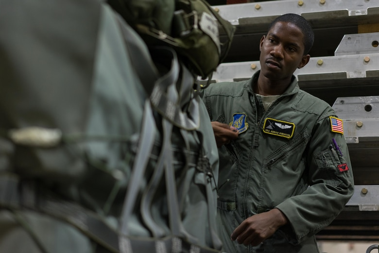 U.S. Air Force Senior Airman Adrian Robinson, 36th Airlift Squadron joint airdrop inspector, inspects the rigging on a container delivery system bundle during Red Flag Alaska on Joint Base Elmendorf-Richardson, Alaska, Aug. 11, 2016. Bundles that are improperly rigged can lead to malfunctions which hold the risk of damaging aircraft, personnel and can lead to mission failure. (U.S. Air Force photo by Staff Sgt. Michael Smith/Released)