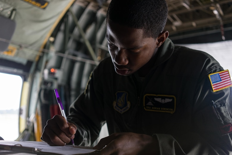 U.S. Air Force Senior Airman Adrian Robinson, 36th Airlift Squadron joint airdrop inspector, signs off on a completed inspection of a container delivery system bundle during Red Flag Alaska on Joint Base Elmendorf-Richardson, Alaska, Aug. 12, 2016. JAI's must perform two inspections; one before loading to ensure cargo is aircraft ready and rigged in accordance with proper rigging procedures and an after inspection of the cargo once it's been completely loaded on the aircraft. (U.S. Air Force photo by Staff Sgt. Michael Smith/Released)