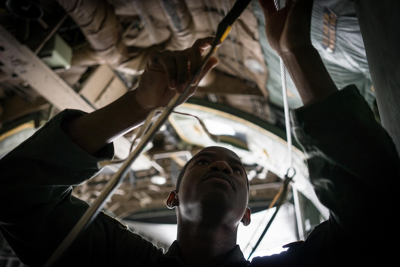 U.S. Air Force Senior Airman Adrian Robinson, 36th Airlift Squadron joint airdrop inspector, inspects the static line rigging on a container delivery system bundle during Red Flag Alaska on Joint Base Elmendorf-Richardson, Alaska, Aug. 12, 2016. Bundles that are improperly rigged can lead to malfunctions which hold the risk of damaging aircraft, personnel and can lead to mission failure. (U.S. Air Force photo by Staff Sgt. Michael Smith/Released)