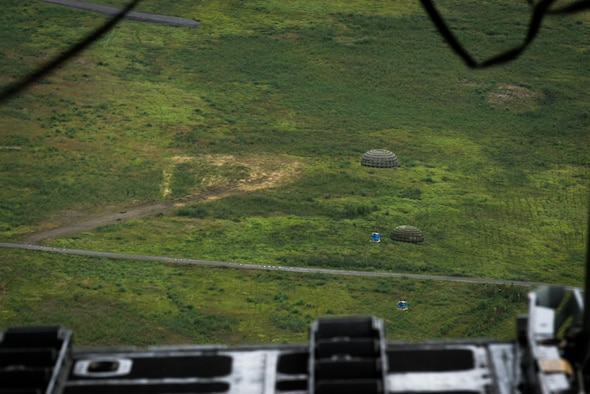 Container delivery system bundles dropped from a C-130 Hercules fall to the drop zone during Red Flag Alaska on Joint Base Elmendorf-Richardson, Alaska, Aug. 12, 2016. Bundles such as these are used to simulate airdrop procedures for supplies to ground forces. (U.S. Air Force photo by Staff Sgt. Michael Smith/Released)