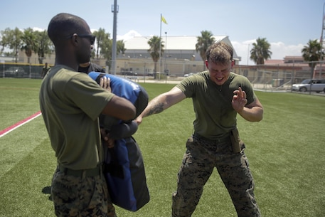 U.S. Marine Corps Lance Cpl. Joe Tomassi a warehouse operator with Special Purpose Marine Air-Ground Task Force Crisis Response-Africa, hits a padded bag with a baton after being sprayed with OC spray during a non-lethal course at Naval Air Station Sigonella, Italy, Aug. 4, 2016. Marines were taught show-of-force tactics, how to restrain a non-combative individual and experienced OC spray and the X-26E TASER during the course. U.S. Marines and Sailors assigned to Special Purpose Marine Air-Ground Task Force-Crisis Response-Africa Command support operations, contingencies and security cooperation in the U.S. Africa Command area of responsibility. (U.S. Marine Corps photo by Cpl. Alexander Mitchell)