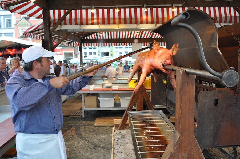 "A cook prepares a roasting pig on a spit as a father with a small child watch him during the annual Pig Burner's festival in Wittlich, Germany, Aug. 12, 2012. More than 200 pigs are sold annually at the popular ""Saeubrenner Kirmes"" in Wittlich, an event that attracts thousands of visitors from Germany and various other countries. (U.S. Air Force photo by Iris Reiff/Released)"