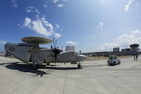 A U.S. Navy E-2C Hawkeye assigned to Carrier Airborne Early Warning Squadron 115, with Carrier Air Wing 5, taxis into hot refueling pits at Marine Corps Air Station Iwakuni, Japan, Aug. 17, 2016. While passing through the air station for aircraft-based training, maintainers inspected and refueled the Hawkeyes before their retrograde back to Naval Air Facility Atusgi.