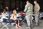 Air Force Lt. Col. Kelly Sullivan and 1st Sgt. Marvin Vides talk to one of numerous residents evacuated to a makeshift shelter in a movie studio near the Celtic Media Centre in Baton Rouge, La., Aug. 15, 2016. Sullivan and Vides are assigned to the Louisiana Air National Guard's 122nd Air Support Operations Squadron. Air National Guard photo by Master Sgt. Dan Farrell