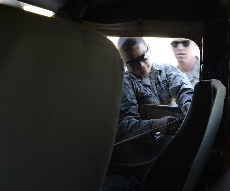 Tech. Sgt. Johnathon Silsley, 921st Contingency Response Squadron civil engineer, learns how to properly secure the doors on a HUMVEE at the Alpena Combat Readiness Training Center at Alpena, Michigan, during Exercise Northern Strike, Aug. 9, 2016. Silsley, stationed at Travis Air Force Base, California, learned how to prepare a HUMVEE before it was lifted by a U.S. CH-47 Chinook. (U.S. Air Force photo by Senior Airman Amber Carter)