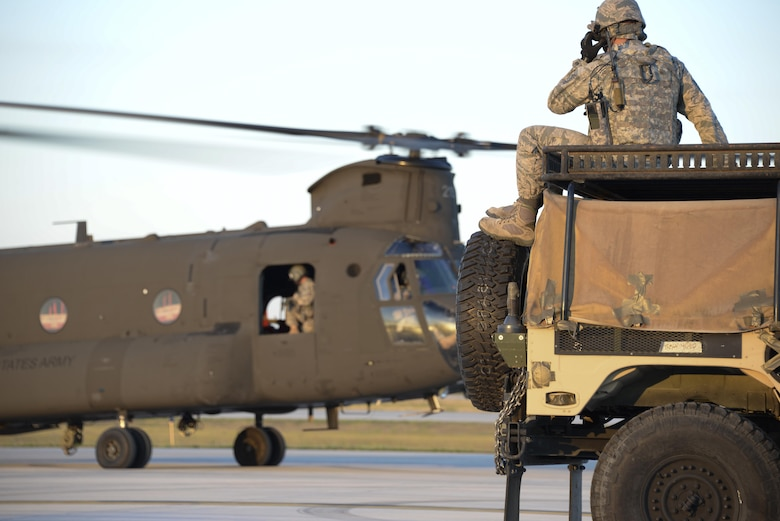 Staff Sgt. William Harden, 921st Contingency Response Squadron ramp coordination instructor, waits for the U.S. Army CH-47 Chinook to takeoff during Exercise Northern Strike at Alpena Combat Readiness Training Center, Michigan, Aug. 9, 2016. Harden, stationed at Travis Air Force Base, California, participated in a sling load exercise to practice attaching a HUMVEE to a Chinook. (U.S. Air Force photo by Senior Airman Amber Carter)