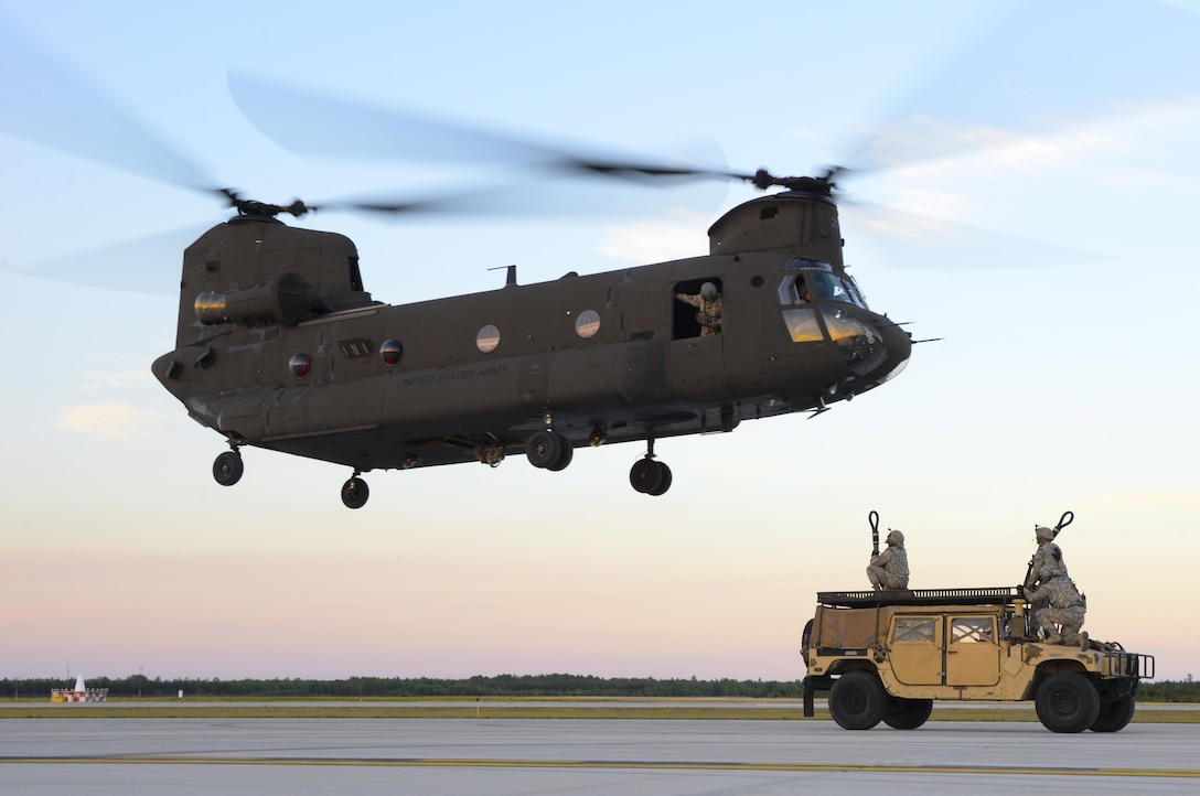 Airmen from the 821st Contingency Response Group out of Travis Air Force Base, California, get positioned to attach a HUMVEE to a U.S. Army CH-47 Chinook at Alpena Combat Readiness Training Center, Michigan, during Exercise Northern Strike, Aug. 9, 2016. Exercise Northern Strike is a large-scale exercise coordinated by the Michigan Army National Guard and features Army, Marines and Air Force working together for total force integration.  (U.S. Air Force photo by Senior Airman Amber Carter)