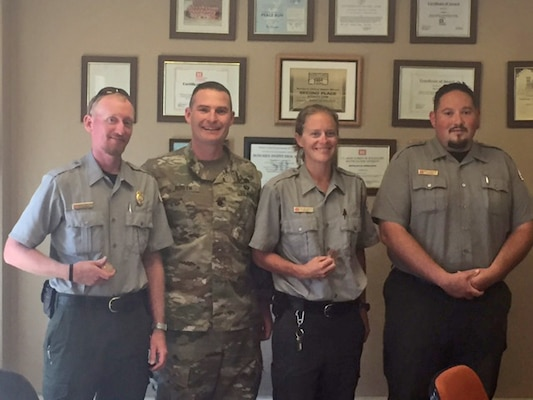 ABIQUIU LAKE, N.M. – District Commander Lt. Col. James Booth presents park rangers (l-r) Austin Kuhlman, Leigh Ann Kirkeeide and Daniel Archuleta with commander's coins, Aug. 12, 2016.  (Ranger Nathaniel Naranjo not pictured). The rangers were recognized for rescuing a man from drowning at the lake on July 30.