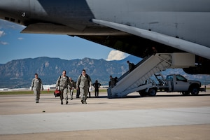 Airmen from the 4th Space Control Squadron disembark a C-5 Galaxy to greet their families at Peterson Air Force Base, Colo., Aug. 13, 2016. The Airmen were deployed overseas and rushed to greet waiting family members. (U.S. Air Force photo by Senior Airman Rose Gudex)