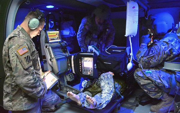 Flight paramedic course instructor Sgt. 1st Class Reid Carpenter (left) wirelessly adjusts the setting of a medical patient simulator as two Army health care specialists, who are paramedic-qualified, practice treating an injured patient inside a UH-60 Blackhawk helicopter trainer. The life-sized trainer offers students the opportunity of realistic classroom exercises emulating the sound, wind, and stressful environment of an actual helicopter. The advanced patient simulators used at AMEDDC&S provide students with vital signs, clinical signs, and symptoms mimicking live patients.