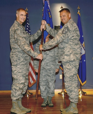 U.S. Air Force Lt. Gen. Scott Williams, Continental U.S. North American Aerospace Defense Command Region and 1st Air Force (Air Forces Northern) Commander, passes the 1AF guidon to Chief Master Sgt. Richard King during the change of authority ceremony at Tyndall Air Force Base, Fla., Aug. 15. King assumed the position from interim Command Chief, Chief Master Sgt. Tiffiney Kellum. (U.S. Air Force photo by Maj. Kat Andrews)