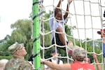 A local camper climbs a rope ladder during the Philly Play Summer Challenge Aug. 10. DLA Troop Support noncommissioned officers and other local military personnel helped children navigate seven obstacle courses during the event.