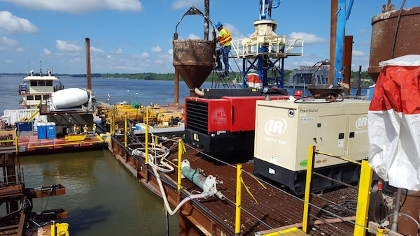 Following the successful set-down of a navigable pass shell, tremie concrete is poured through the lift frame legs to tie the foundation pilings and shell together, thus making it a permanent feature on the river bottom. The tremie mix is specially designed to withstand the underwater environment encountered on the bottom of the Ohio river while maintaining a consistent flow and strength.
