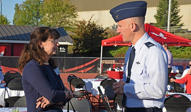 Col. Ryan Samuelson, 92nd Air Refueling Wing commander, discusses the importance of Fairchild Air Force Base's relationship with the community with Dr. Mary Cullinan, Eastern Washington University president, during the monthly West Plains Chamber of Commerce Breakfast Aug. 17, 2016, in Cheney, Wash. This month's breakfast was held at EWU's Roos Field to kick off the Eagles' upcoming football season. (U.S. Air Force Photo/Airman 1st Class Mackenzie Richardson)