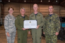Major-General Christian Drouin, Commander of 1 Canadian Air Division, and General Lori Robinson, Commander of the North American Aerospace Defense Command and U.S. Northern Command,  presents a NORAD commendation to the 4 Wing Base Commander Colonel Paul Doyle and Acting 4 Wing Chief Warrant Officer Robert Brassington, at Hangar 1, 4 Wing Cold Lake, Alberta, Canada, Aug. 15, 2016.