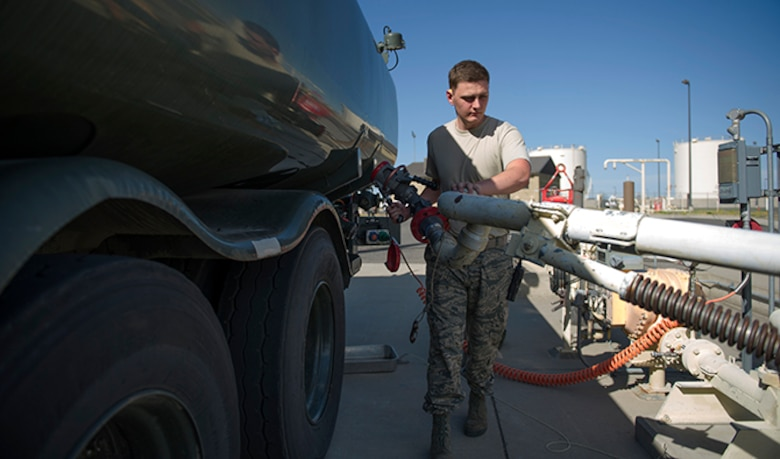 Airman 1st Class Michael Peek, 92nd Logistics Readiness Squadron refueling equipment operator, wrangles a pipe hookup from a pumping station to a R-11 fuel tanker truck July 26, 2016, at Fairchild Air Force Base, Wash. Vital to ensure that no contaminants make it into aircraft, fuels airmen check fuel purity regularly. (U.S. Air Force photo/ Airman 1st Class Sean Campbell)