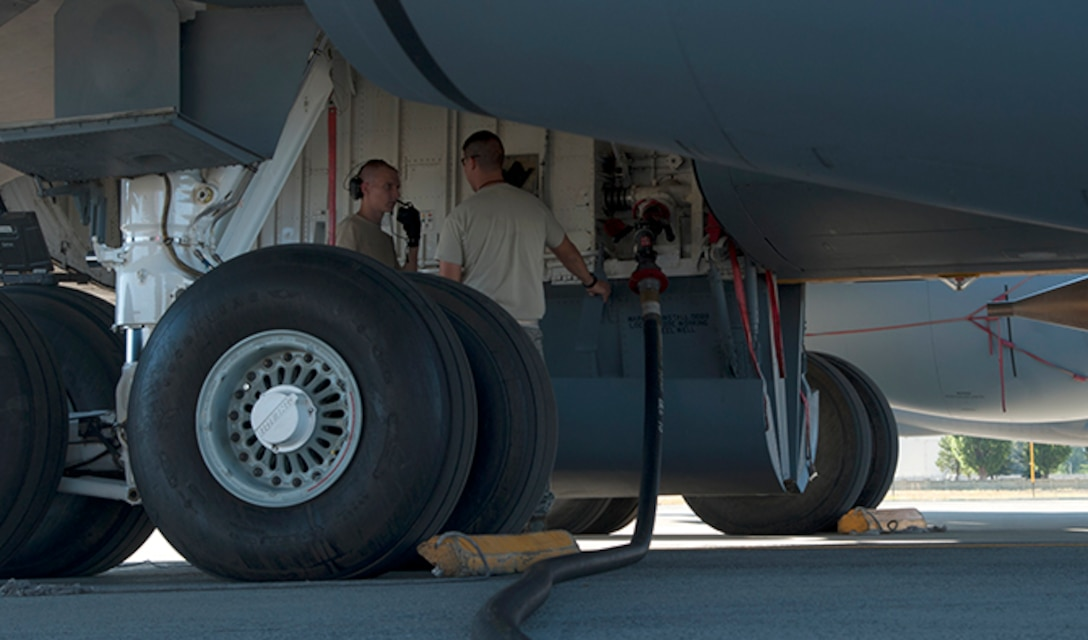 Airman 1st Class Thomas Fisher, 92nd Maintenance Group crew chief, discusses checklist items with another crew chief as his assigned KC-135 is being refueled Aug. 16, 2016, at Fairchild Air Force Base, Wash. Refueling actions on a dry KC-135 may take approximately an hour or longer depending on the demand for fuel at a given time. (U.S. Air Force photo/ Airman 1st Class Ryan Lackey)