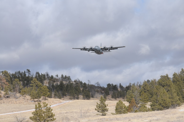 A C-130H Hercules aircraft assigned to the 153rd Airlift Wing, Wyoming Air National Guard flies over Camp Guernsey, Wyoming during Modular Airborne Fire Fighting System training. The training is being performed using a C-130 modified with an Electronic Propeller Control System and eight-bladed propeller system. (Courtesy photo)