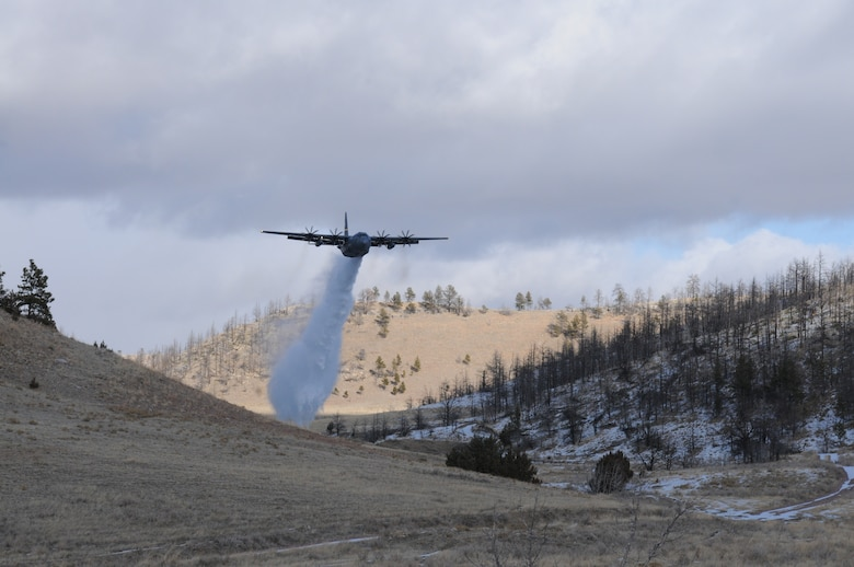 A C-130H Hercules aircraft assigned to the 153rd Airlift Wing, Wyoming Air National Guard sprays water over Camp Guernsey, Wyoming during Modular Airborne Fire Fighting System training. The training is being performed using a C-130 modified with an Electronic Propeller Control System and eight-bladed propeller system. (Courtesy photo)