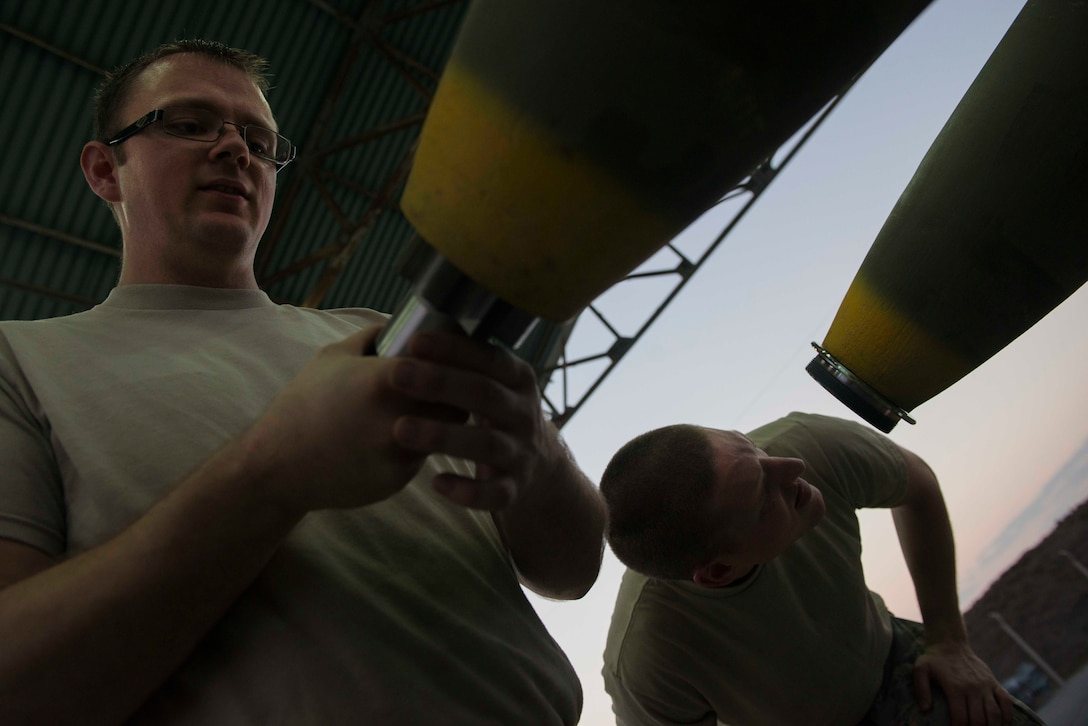 U.S. Air Force Tech. Sgt. Andrew Danielson (left) and Staff Sgt. Shadrach Mchargue, 447th Expeditionary Aircraft Maintenance Squadron munitions systems specialists, prepare GBU-12 Paveway II laser-guided bombs for transport Aug. 8, 2016, at Incirlik Air Base, Turkey. Upon completion, munitions are transported to either aircraft or storage. (U.S. Air Force photo by Senior Airman John Nieves Camacho)