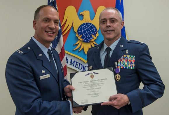 Col. Douglas Curry, 375th Medical Group commander presents Lt. Col. Steven Fisher with the Purple Heart during a ceremony on Aug. 12, 2016 at Scott Air Force Base, Ill. On Oct. 17, 2011 Fisher was injured in the line of duty during a rocket attack while deployed to Afghanistan. (U.S. Air Force Photo by Airman Daniel Garcia)