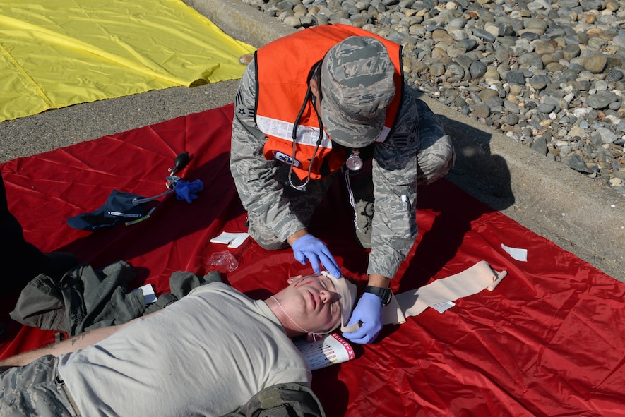 A first responder wraps a head wound of an Airman during an active shooter exercise Aug. 17, 2016, at Beale Air Force Base, California. The exercise evaluated Beale first responders actions if an occurrence, such as an active shooter, were to happen on the installation. (U.S. Air Force photo by Senior Airman Ramon A. Adelan)