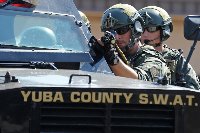 A Yuba County Sheriff's Department SWAT member draws his weapon and evaluates the scene of an active shooter exercise Aug. 17, 2016, at Beale Air Force Base, California. Beale personnel and Yuba County SWAT worked cohesively to extract individuals on lockdown and eliminate the simulated threat. (U.S. Air Force photo by Senior Airman Ramon A. Adelan)