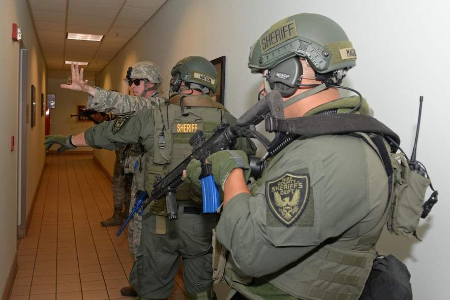 A 9th Security Forces Squadron member briefs a Yuba County Sheriff's Department SWAT member on the current situation of an active shooter exercise Aug. 17, 2016, at Beale Air Force Base, California. Beale personnel and Yuba County SWAT worked cohesively to extract individuals on lockdown and eliminate the simulated threat. (U.S. Air Force photo by Senior Airman Ramon A. Adelan)