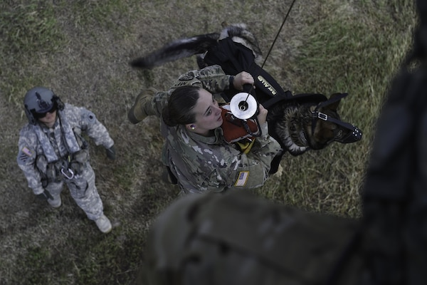 U.S. Army Spc. Mariah Ridge, a military working dog handler assigned to Joint Task Force-Bravo's Joint Security Forces, and her MWD, Jaska, ride a hoist to a UH-60L Black Hawk during training at Soto Cano Air Base, Honduras, August 15, 2016. Ridge was one of three MWD handlers who trained on hoist operations for the first time with their dogs.