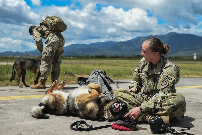 U.S. Army Spc. Mariah Ridge, a military working dog handler assigned to Joint Task Force-Bravo's Joint Security Forces, laughs at her MWD, Jaska, during K9 hoist evacuation training at Soto Cano Air Base, Honduras, August 15, 2016. Although the MWDs and their handlers were training in 90 degree, 100 percent humidity weather, they managed to stay in good spirits.