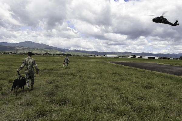 U.S. Army Spc. Harley Reno, a military working dog handler assigned to Joint Task Force-Bravo's Joint Security Forces, and his MWD, walk toward a UH-60L Black Hawk during K9 hoist evacuation training at Soto Cano Air Base, Honduras, August 15, 2016. The MWDs and their handlers undergo the hoist training so their first experience with a helicopter won't come during a real-world operation.