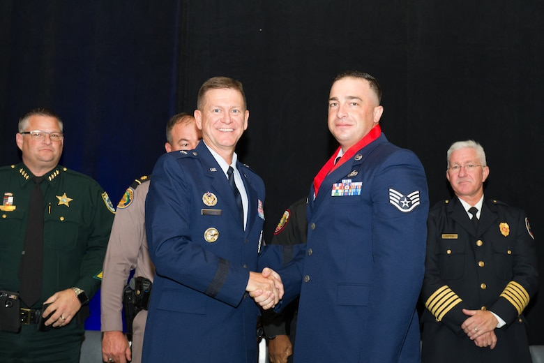 Brig. Gen. Wayne Monteith, 45th Space Wing commander, assists the Melbourne Regional Chamber of East Central Florida with the presentation of the Life Saving Medal to Staff Sgt Michael Hempill, of the 45th Space Wing Civil Engineer Squadron, at the chamber's Valor Awards banquet on Aug. 17, 2016.  While off duty and fishing at Patrick Air Force Base's Outdoor Recreation on base area with family and friends Hemphill immediately responded to another family's cry for help after a man fell out of his kayak. (U.S. Air Force photos/Benjamin Thacker/Released)
