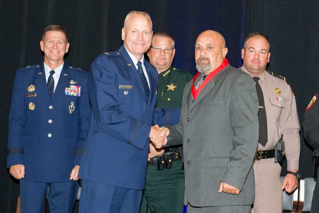 "James R. ""Bob"" Wallace (right) is presented with the Medal of Valor by Col. Jeffrey W. Dyball (left) at a ceremony hosted by the Melbourne Regional Chamber of East Central Florida Aug. 17, 2016.  Wallace, a member of the Air Force Technical Applications Center at Patrick AFB, Fla., received the recognition for selflessly rendering aid to a disabled motorist on a busy interstate highway.  While doing so, Wallace was struck by another vehicle, was hospitalized in critical condition, underwent multiple surgeries and months of rehabilitation. (U.S. Air Force photos/Benjamin Thacker/Released)"