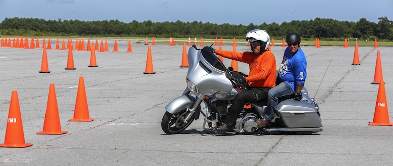 Steve Schuiber, front, a Moto Mark 1 Motorcycle Skill Enhancer instructor, demonstrates to Gunnery Sgt. Chris Foster, a course participant, the precision needed to handle the simulated course in a 'Bike Safe' street situational environment at Marine Corps Auxiliary Landing Field Bogue, North Carolina, Aug. 14. Bike Safe is a proactive approach to engage motorcyclist before they do something that's unsafe. (U.S. Marine Corps photo by Lance Cpl. Tavairus Hernandez /Released)