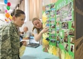 Tech. Sgt. Jennifer, the Non-Commissioned Officer In-Charge of Emergency Management, listens to Staff Sgt. Ashley, a sensor operator from the 9th Attack Squadron here, shows pictures of the project her team, The Knights, did during the Big Give as part of the Big Give after-party August 12, 2016 at Holloman Air Force Base, N.M. Over the course of three weeks, 32 teams of 412 participants spent nearly 5,000 man hours volunteering in the local community — saving the area $202,092.33. (Last names are being withheld due to operational requirements. U.S. Air Force photo by Airman 1st Class Randahl J. Jenson)