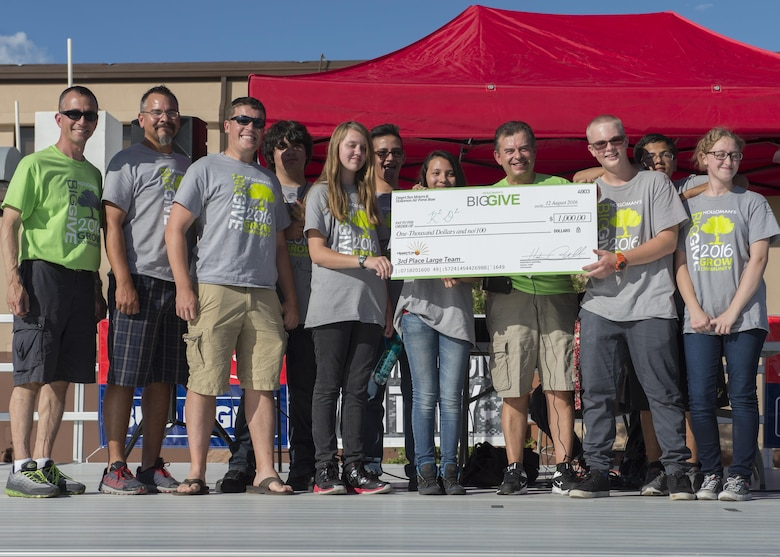 Members from the 6th Attack Squadron's R2D2 receive their $1,000 reward for winning the Third Place Large Team Award at the Big Give after-party August 12, 2016 at Holloman Air Force Base, N.M. Over the course of three weeks, 32 teams of 412 participants spent nearly 5,000 man hours volunteering in the local community — saving the area $202,092.33. (U.S. Air Force photo by Airman 1st Class Randahl J. Jenson)