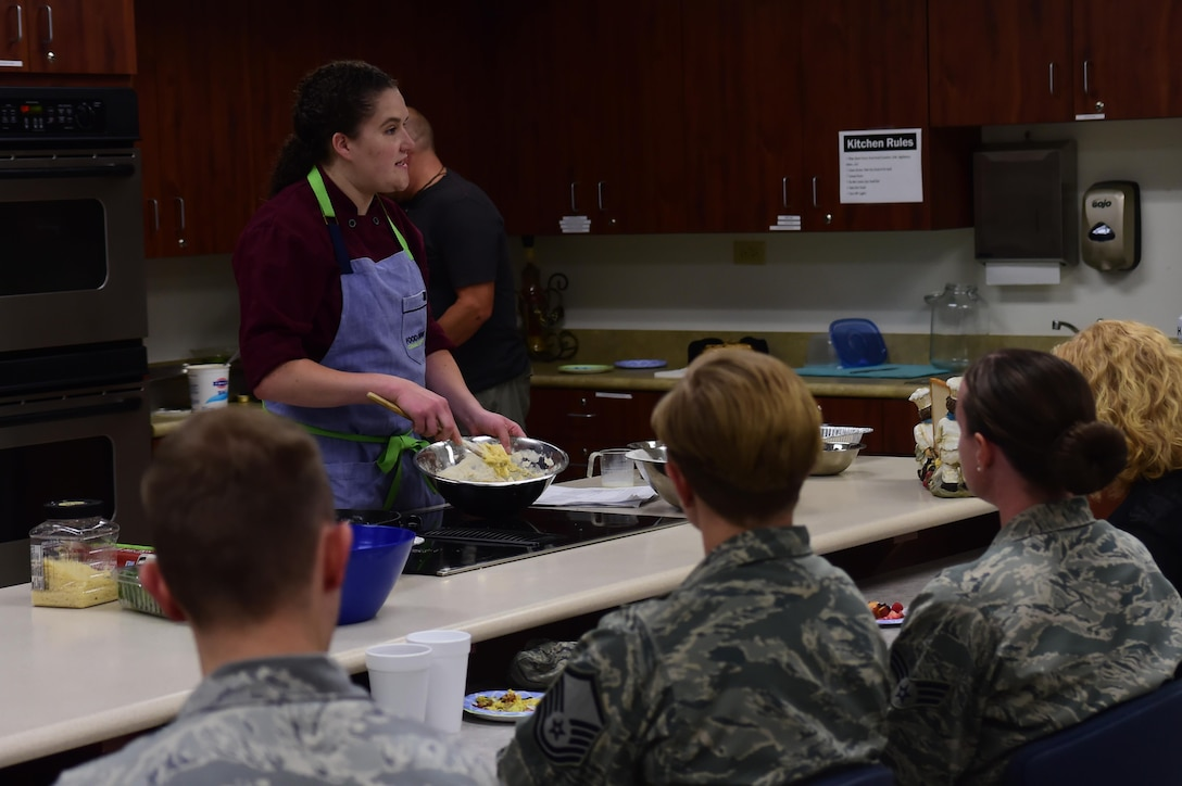 Charlotte Muller, Whole Foods chef, demonstrates to an audience how to prepare a blueberry crumble cake August 18, 2016, at the Health and Wellness Center on Buckley Air Force Base, Colo. Members of Team Buckley were invited to enjoy a meal while also learning how to prepare it during the 460th Medical Group's monthly cooking demonstration. (U.S. Air Force photo by Senior Airman Luke W. Nowakowski/Released)