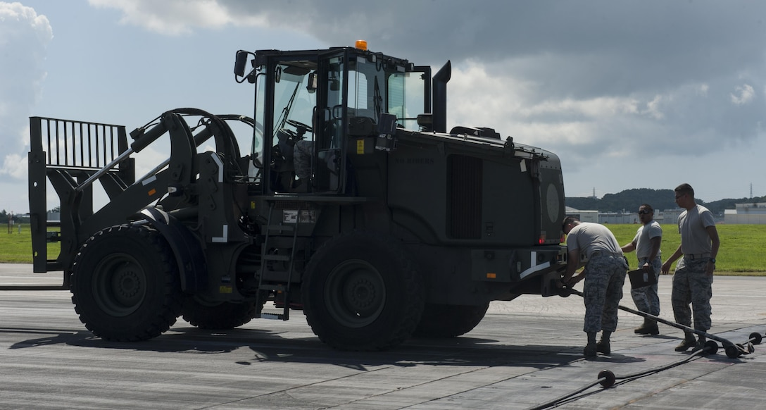 Airmen from the 18th Civil Engineer Squadron prepare for aircraft barrier training Aug. 16, 2016, at Kadena Air Base, Japan. The 18th CES conducted aircraft barrier training to ensure preparedness in the event of an in-flight emergency. The aircraft barrier is designed to catch an aircraft as it lands on the flightline.  (U.S. Air Force photo by Airman 1st Class Lynette M. Rolen)
