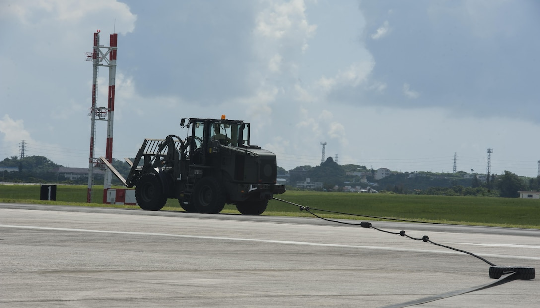 Staff Sgt. Fardad Alimehri, 18th Civil Engineer Squadron electrical power production and barrier maintenance technician, simulates an aircraft landing on an aircraft barrier Aug. 16, 2016, at Kadena Air Base, Japan. The aircraft barrier catches an aircraft as it makes its landing, ensuring security for the aircraft and pilot. (U.S. Air Force photo by Airman 1st Class Lynette M. Rolen)