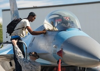 U.S. Air Force Senior Airman Christopher Tidline, a 354th Maintenance Squadron aircrew egress technician, peels a decal from an F-16 Fighting Falcon aircraft while cross-utilizing his time to supplement a crew chief's position with the 354th Aircraft Maintenance Squadron, Aug. 17, 2016, at Eielson Air Force Base, Alaska. Tidline will work more than 100 hours with the sister squadron who maintains 18th Aggressor Squadron aircraft in support of RED-FLAG-Alaska 16-3, so pilots can share their knowledge of flying with participating units in the exercise. (U.S. Air Force photo by Staff Sgt. Shawn Nickel)