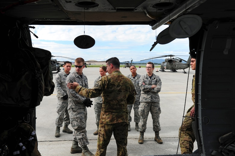 U.S. Airmen assigned to the 354th Medical Operations Squadron at Eielson Air Force Base, Alaska, receive instructions on transporting a casualty to a helicopter during joint training Aug. 12, 2016, outside Hangar 6 on Ladd Army Airfield at Fort Wainwright, Alaska. This portion of the training was conducted with U.S. Army UH-60 Black Hawk helicopter and it medevac crew. (U.S. Air Force photo by Airman Isaac Johnson)