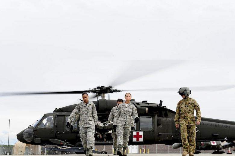 U.S. Air Force Airmen assigned to the 354th Medical Operations Squadron at Eielson Air Force Base, Alaska, transport a simulated casualty from a U.S. Army UH-60 Black Hawk helicopter during joint training Aug. 12, 2016, outside Hangar 6 at Ladd Army Airfield on Fort wainwright, Alaska. The height of the people carrying the casualty should be properly distributed to keep the simulated casualty safe as they are transported from the helicopter. (U.S. Air Force photo by Airman Isaac Johnson)