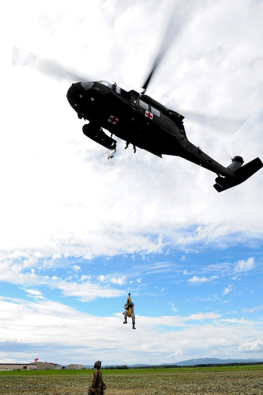 U.S. Air Force Senior Airman Roxanne Lawrence, a 354th Medical Operations Squadron nurse technician, assigned to Eielson Air Force Base, Alaska hovers under a U.S. Army UH-60 Black Hawk helicopter during medical evacuation training Aug. 12, 2016, outside Hangar 6 on Ladd Army Airfield at Fort Wainwright, Alaska. The hoist on this helicopter can carry more than 450 pounds, which allows medical personnel to bring casualties onto a hovering aircraft. (U.S. Air Force photo by Airman Isaac Johnson)