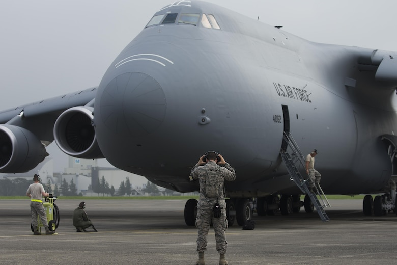 Members with the 621st Contingency Response Squadron conduct preflight checks on a C-5M Super Galaxy at Yokota Air Base, Japan, Aug. 16, 2016. The 621 CRS sent crew chief to Yokota to gain proficiency and training on a range of aircraft, working alongside the 730th Air Mobility Squadron. The 730 AMS often works with C-5, C-17A Globemaster III, KC-135 Stratotanker, KC-10A Extender and civilian aircraft. (U.S. Air Force photo by Yasuo Osakabe/Released)
