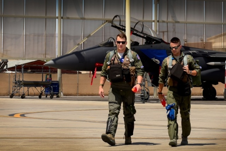 U.S. Air Force 1st Lieutenant Drew Lyons, 492nd Fighter Squadron, F-15E Strike Eagle pilot, and 1st Lieutenant J. Paul Reasner, 492nd FS, F-15E Strike Eagle weapon systems officer, step to their aircraft for a sortie in support of exercise Red Flag 16-4 at Nellis Air Force Base, Nev. Aug 17. Red Flag is the U.S. Air Force's premier air-to-air combat training exercise and one of a series of advanced training programs that is administered by the U.S. Air Force Warfare Center and executed through the 414th Combat Training Squadron. (U.S. Air Force photo/ Tech. Sgt. Matthew Plew)